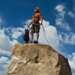 Rock climber nearing the summit. - Stock Photo