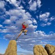 Climber jumping across gap. - Stock Photo