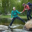 Hikers crossing a stream. - Stock Photo