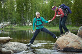 Hikers crossing a stream. — Stock Photo