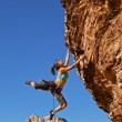 Female rock climber clinging to a cliff. - Stock Photo