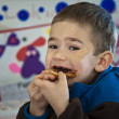 Young boy eating a sandwich. - Stock Photo