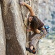 Royalty-Free Stock Photo: Female climber clinging to a cliff.