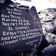 A proverb chiseled onto a rock in the desert. - Stock Photo