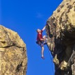 Stock Photo: Climber clinging to cliff.