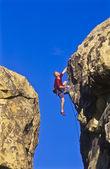 Alpinista se agarrando a um penhasco. — Fotografia Stock