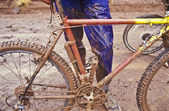 Muddy mountain bike and rider. — Stock Photo