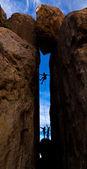 Team of climbers struggel up a steep cliff. — Stock Photo
