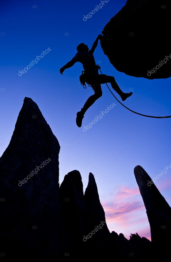 A climber dangles from the edge of an overhanging rock in The Sierra Nevada Mountains, California.  Photo #5941451