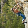 Female climber clinging to a cliff. — Stock Photo