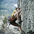 Stock Photo: Rock climber clinging to cliff.