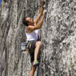 Постер, плакат: Rock climber clinging to a cliff