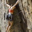 Female climber clinging to a cliff. — Stock Photo #6410154