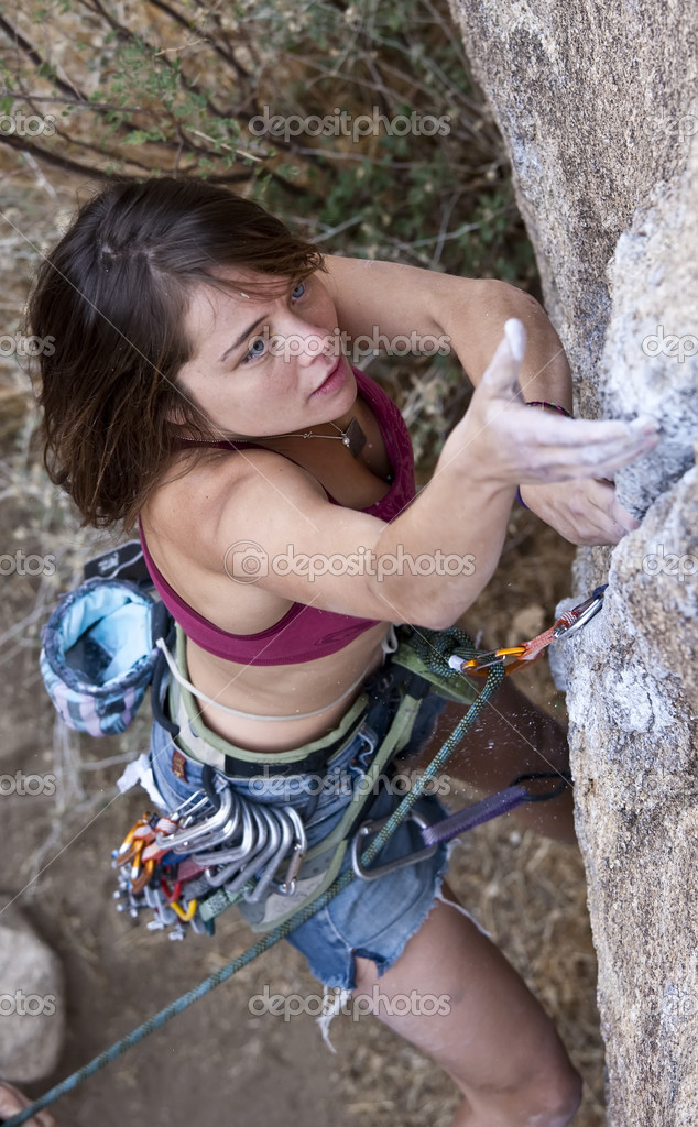 Female rock climber is focused on her next move as she battles her way up a steep cliff in Joshua Tree National Park, California. — Stock Photo #6446422
