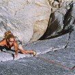 Stock Photo: Female climber clinging to a cliff.