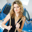 Young woman in the showroom with a new car with ropes on their shoulders — Stock Photo