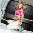 Royalty-Free Stock Photo: Pretty young woman in ropes in cargo van inside