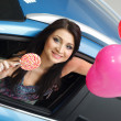 Young woman with candy and heart baloons with New car — Stock Photo