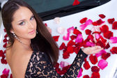 Young woman with New car in red rose petals — Stock Photo