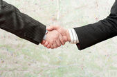 Handshake on the map background — Stock Photo