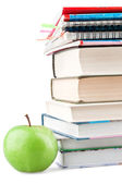 Textbooks and notebooks next to the green apple — Стоковое фото