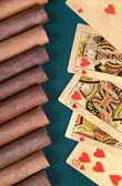 Cigars and playing cards on green baize.. — Stock Photo