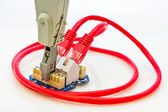 Red network cable and punch down tool in the wall outlet — Stock Photo