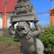 Unfinished statue at the entrance to a Buddhist complex - Stock Photo