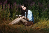 The woman reads the book on the nature — Stock Photo