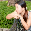 Stock Photo: Asiwomen distracted on bench in park