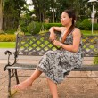 Asian women distracted on bench in park — Stock Photo
