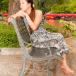 Stock Photo: Distracted Asiwomen sitting on bench in park from side