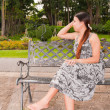 Stock Photo: Asiwomen distracted on bench in park faced right