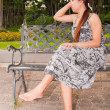 Stock Photo: Asiwomen distracted on bench in park faced rightfit frame