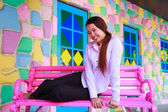 Asian young women sitting on pink chair — Stock Photo