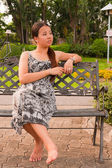 Distracted Asian women sitting on bench in park faced left — Stock Photo