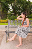 Asian women distracted on bench in park faced right — Stock Photo