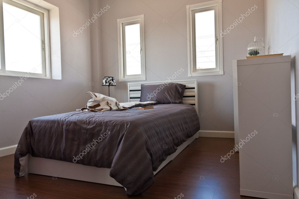 White bedroom with brown sheet bed and many windows — Stock Photo #6377125
