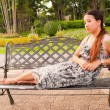 Stock Photo: Distracted Asiwomen lay down on bench in park