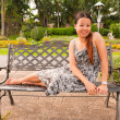 Young asian women sitting and smile on bench in park - Stock Photo