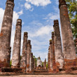 Stock Photo: Buddhstatue among pillars from back worm