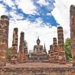 Buddha statue among pillars - Foto Stock