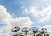 Satellite receiver pointing into blue sky — Stock Photo