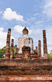 Buddha statue among pillars from back worm vertical — Stock Photo
