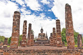 Buddha statue among pillars — Stock Photo