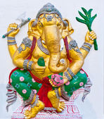 Golden ganesha with weapons on white wall — Stok fotoğraf