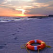 Ring buoy lying on the sandy beach — Stock Photo
