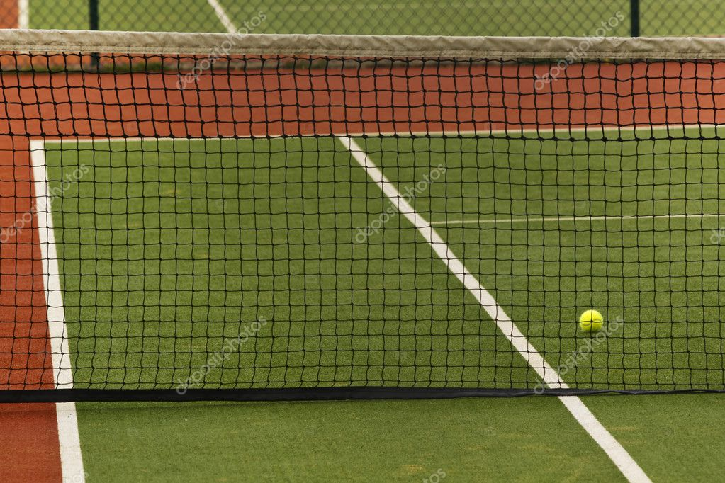 A tennis ball on a court behind a net — Stock Photo #6644600