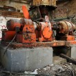 Orange machine inside abandoned building - Stock Photo