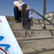 Stock Photo: Skateboarder sitting on stairs